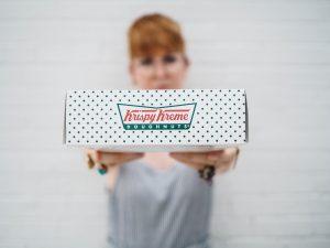 Woman holding box of Krispy Kreme donuts; image by The Creative Exchange, via Unsplash.com.