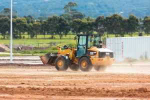 Digger at work at residential estate development; image by Troy Mortier, via Unsplash.com.