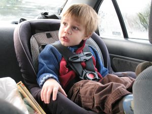 Young boy in a car seat; image by xordroyd, via Flickr, CC BY-SA 2.0, no changes.
