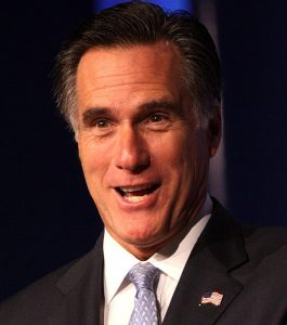 Mitt Romney grinning, wearing a dark suit.