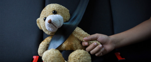 Teddy bear wearing a seatbelt, hand held by a child; image courtesy of Lex Machina.