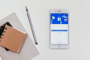 Notepads, pen, and smartphone with Facebook on the screen; image by freestocks.org, via Pexels.com.