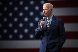 Joe Biden wearing a suit, in front of an American Flag backdrop.