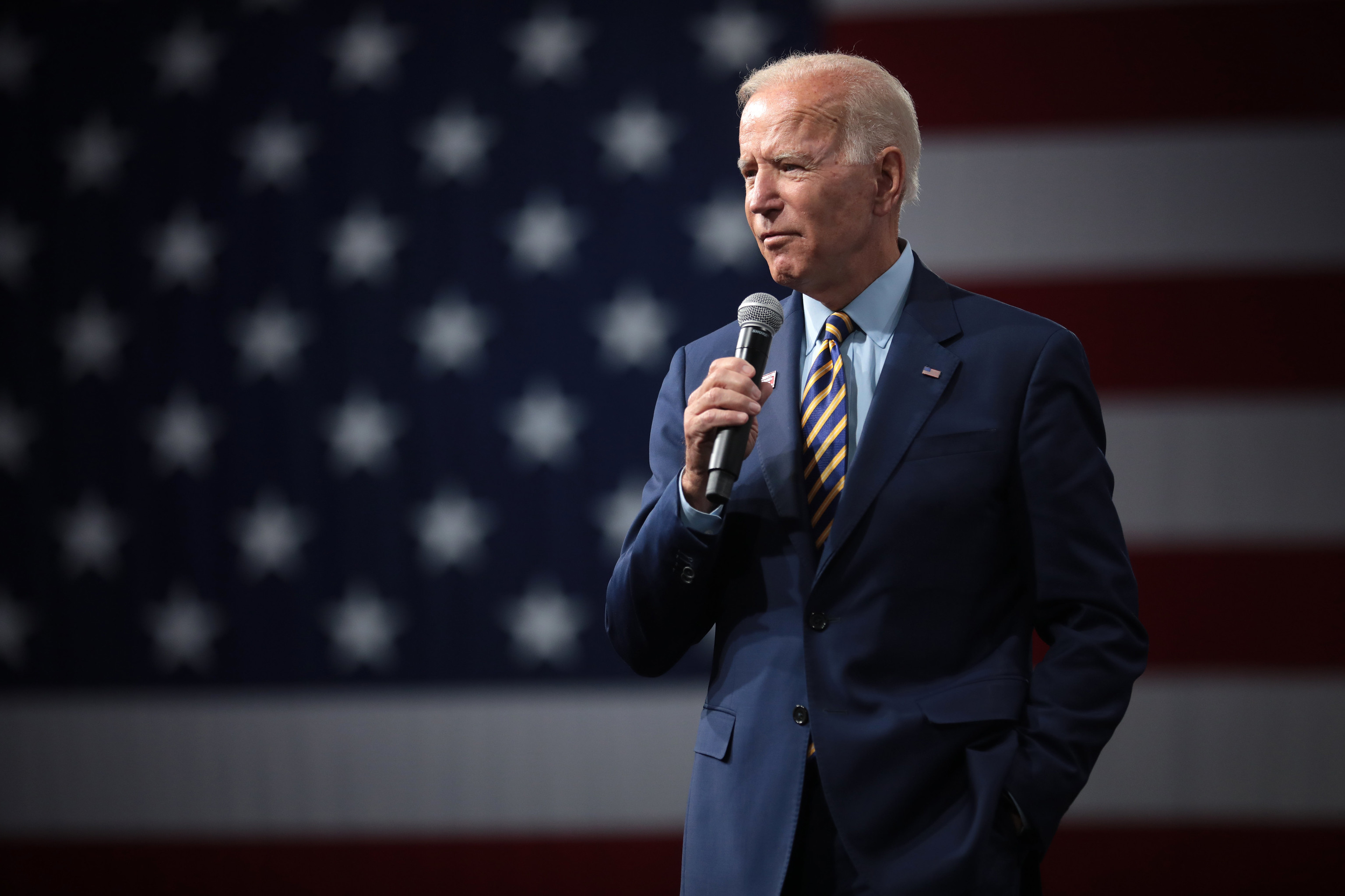 Joe Biden wearing a suit, in front of an American Flag backdrop.