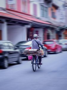 Man on bicycle riding past parked cars; image by Adeline Lee, via Unsplash.com.