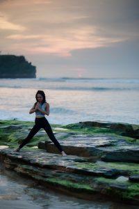 Woman doing yoga by the shore; image by bady qb, via Unsplash.com.