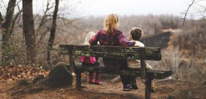 Woman and two children on a park bench; image by Benjamin Manley, via Unsplash.com.