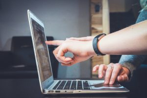 Two people reviewing something on a laptop; image by John Schnobrich, via Unsplash.com.