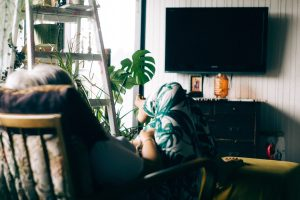 Woman sitting in chair in front of TV; image by John Tuesday, via Unsplash.com.