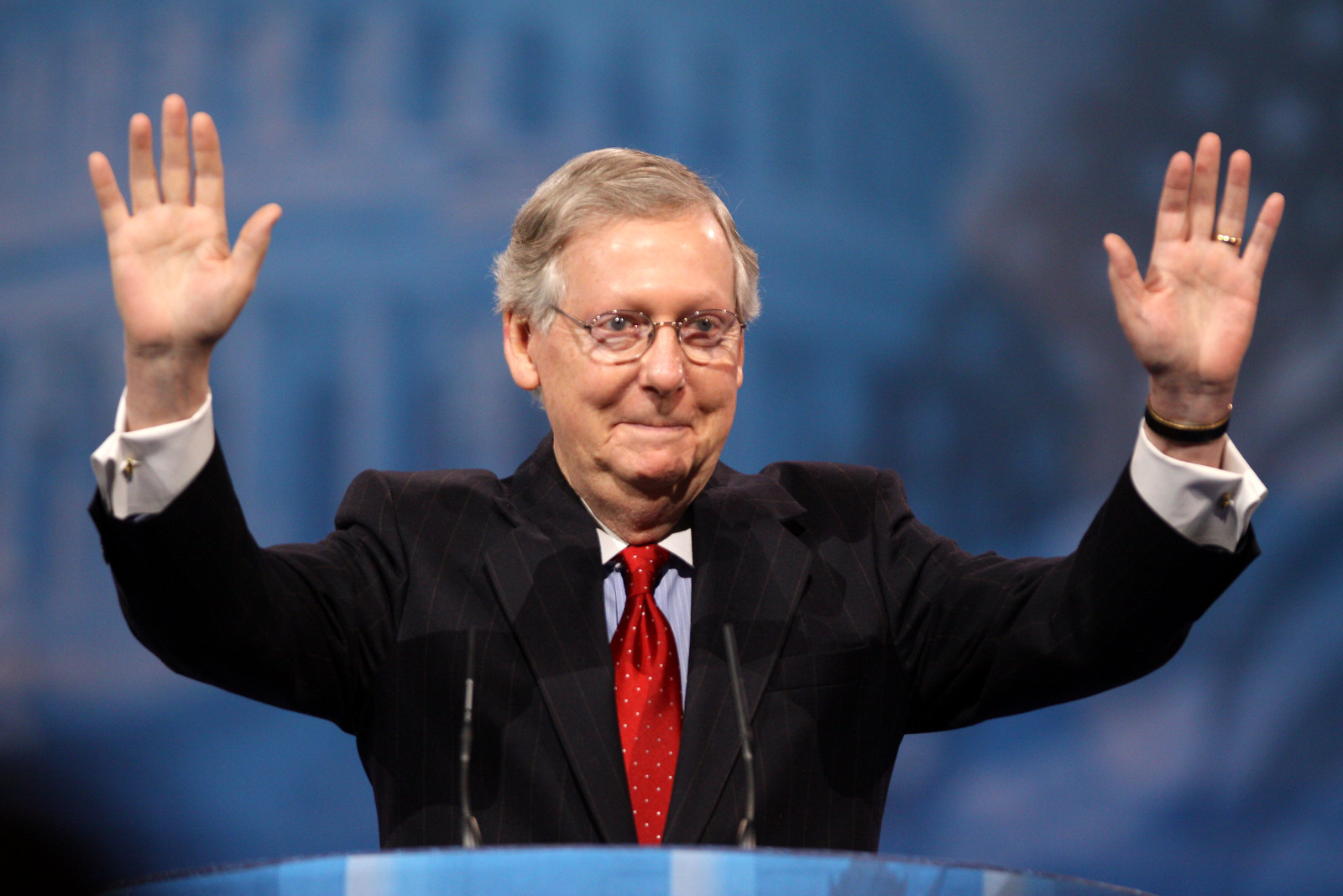 A greying, older man in a dark suit, at a podium, with his hands raised.