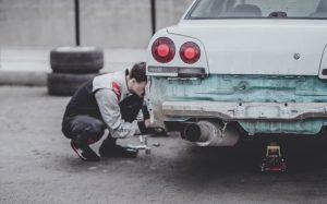 Man fixing car; image by Arseny Togulev, via Unsplash.com.