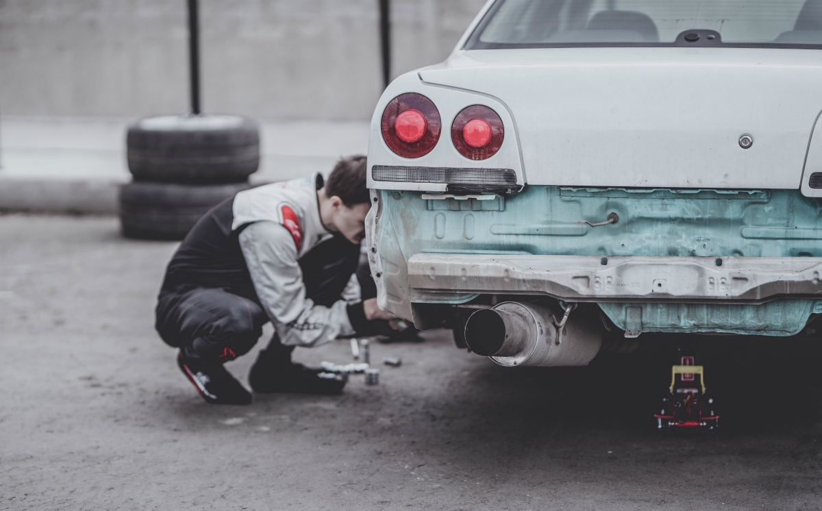Man fixing car; image by Arseny Togulev, via Unsplash.com.