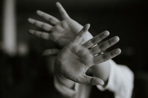 Woman holding both hands out, palms first; image by M.T ElGassier, via Unsplash.com.