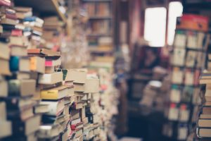 Piles of old books; image by Eli Francis, via Unsplash.com.