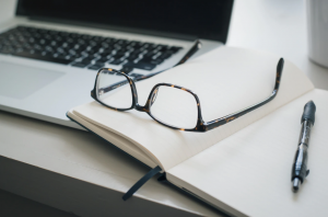 Laptop, notebook, pen, and reading glasses; image by Trent Erwin, via Unsplash.com.