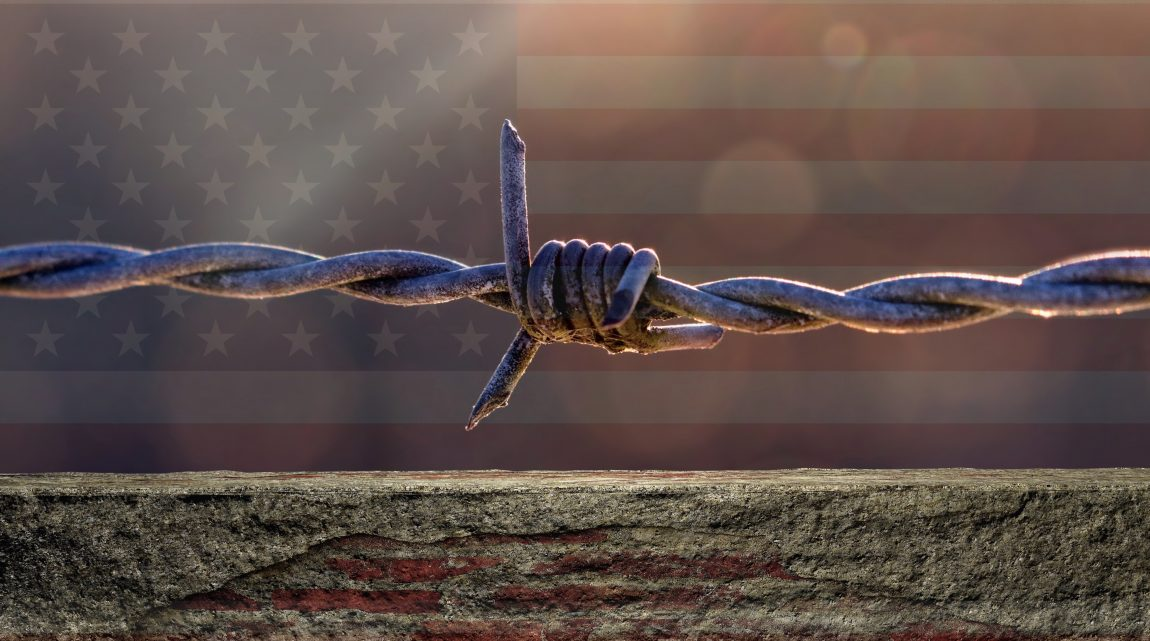 A wall topped with a strand of barbed wire, with a shadowy American flag in the distant background.