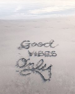 """Good Vibes Only"" written in the sand by the sea; image by Ashley Whitlatch, via Unsplash.com."