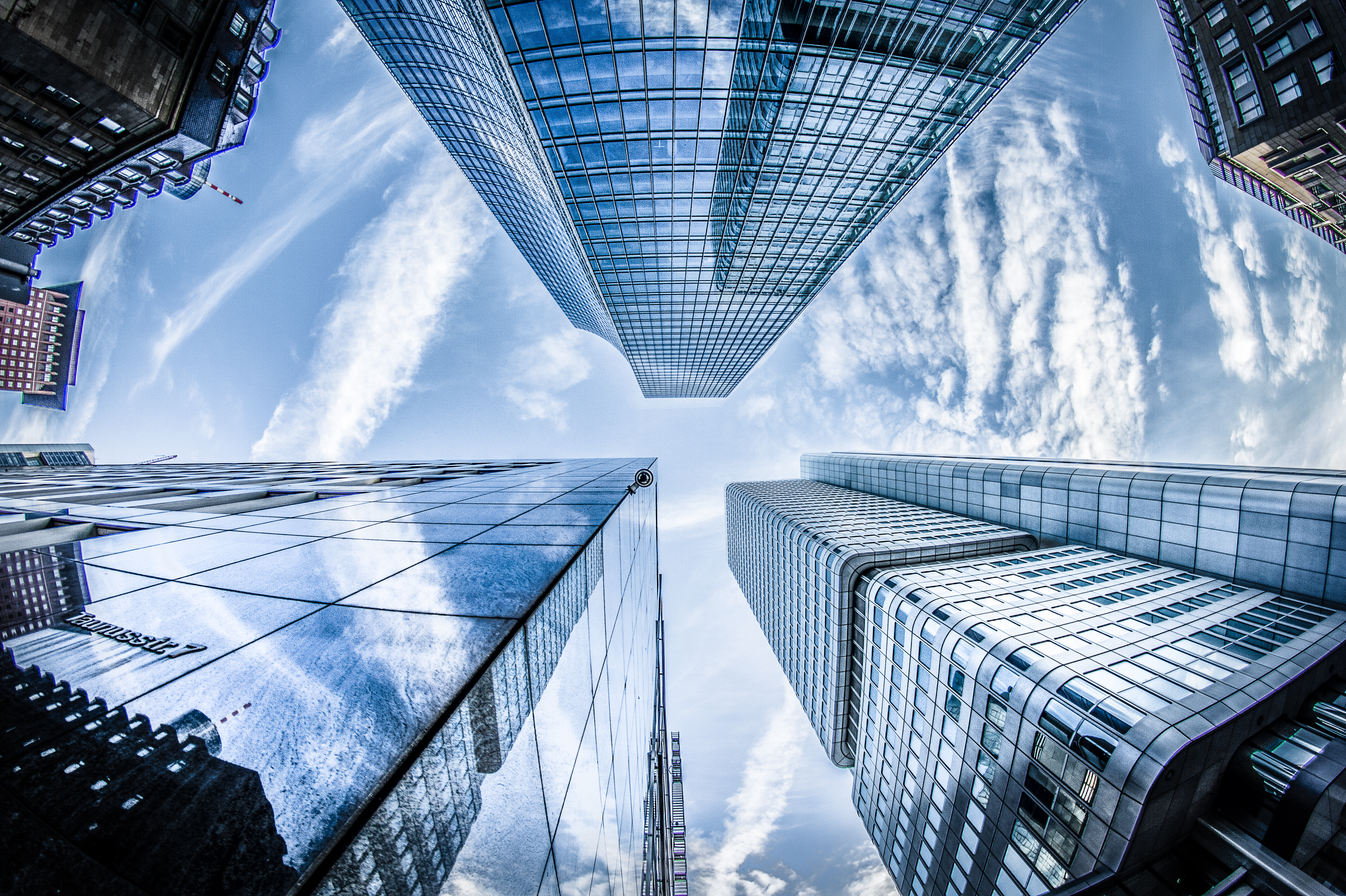 Ground view looking up of glass buildings; image by Philipp Birmes, via Unsplash.com.