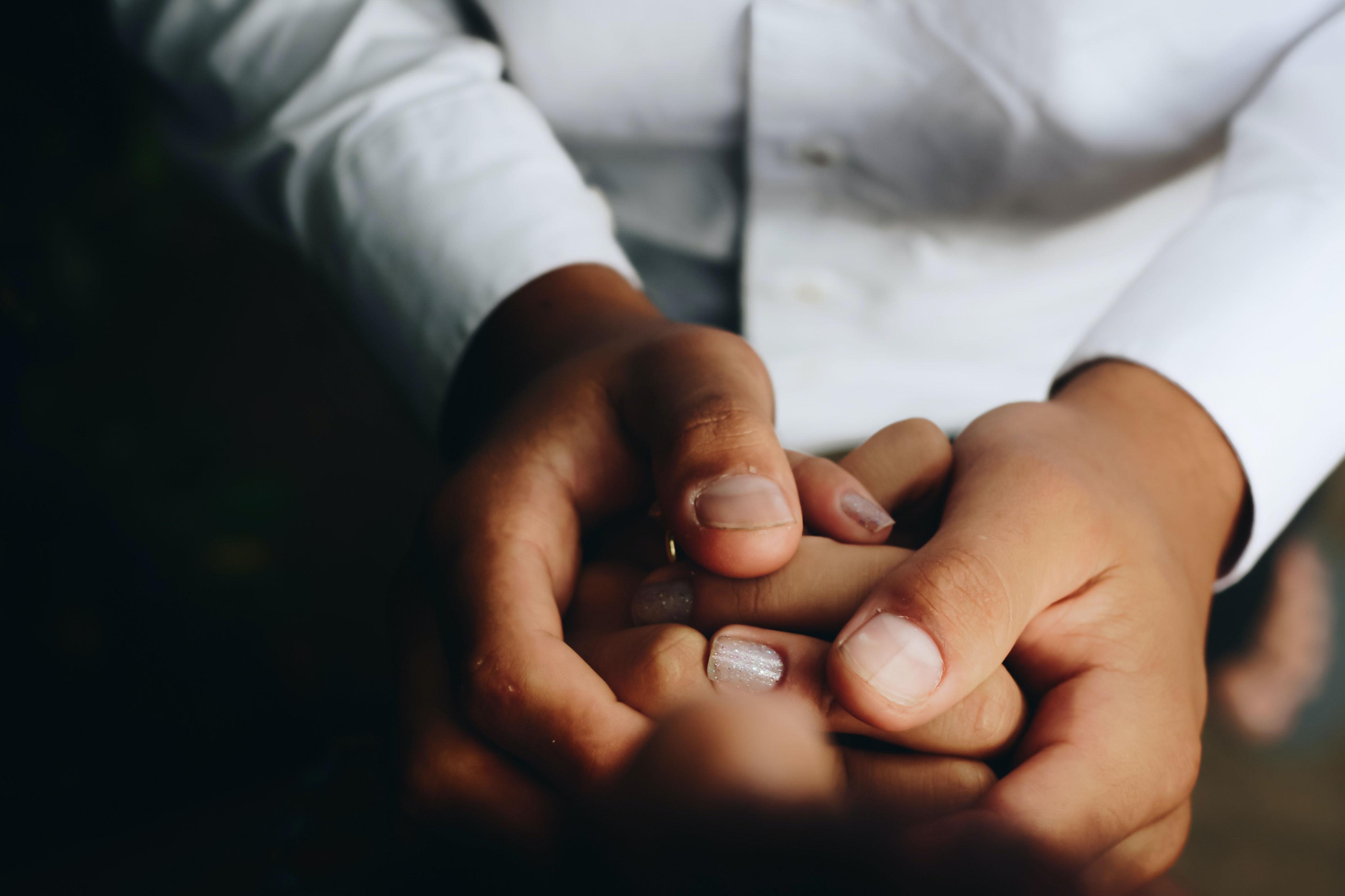 People holding hands; image by Matheus Ferrero, via Unsplash.com.