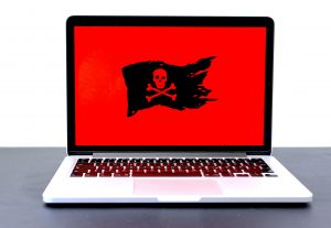 Laptop displaying a pirate flag / jolly roger on a red screen, possibly indicating malware, hackers or a different computer problem. Image by Michael Geiger, via Unsplash.com.