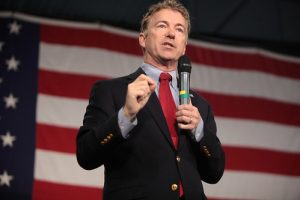 A man in a suit speaks into a microphone in front of a large American flag.