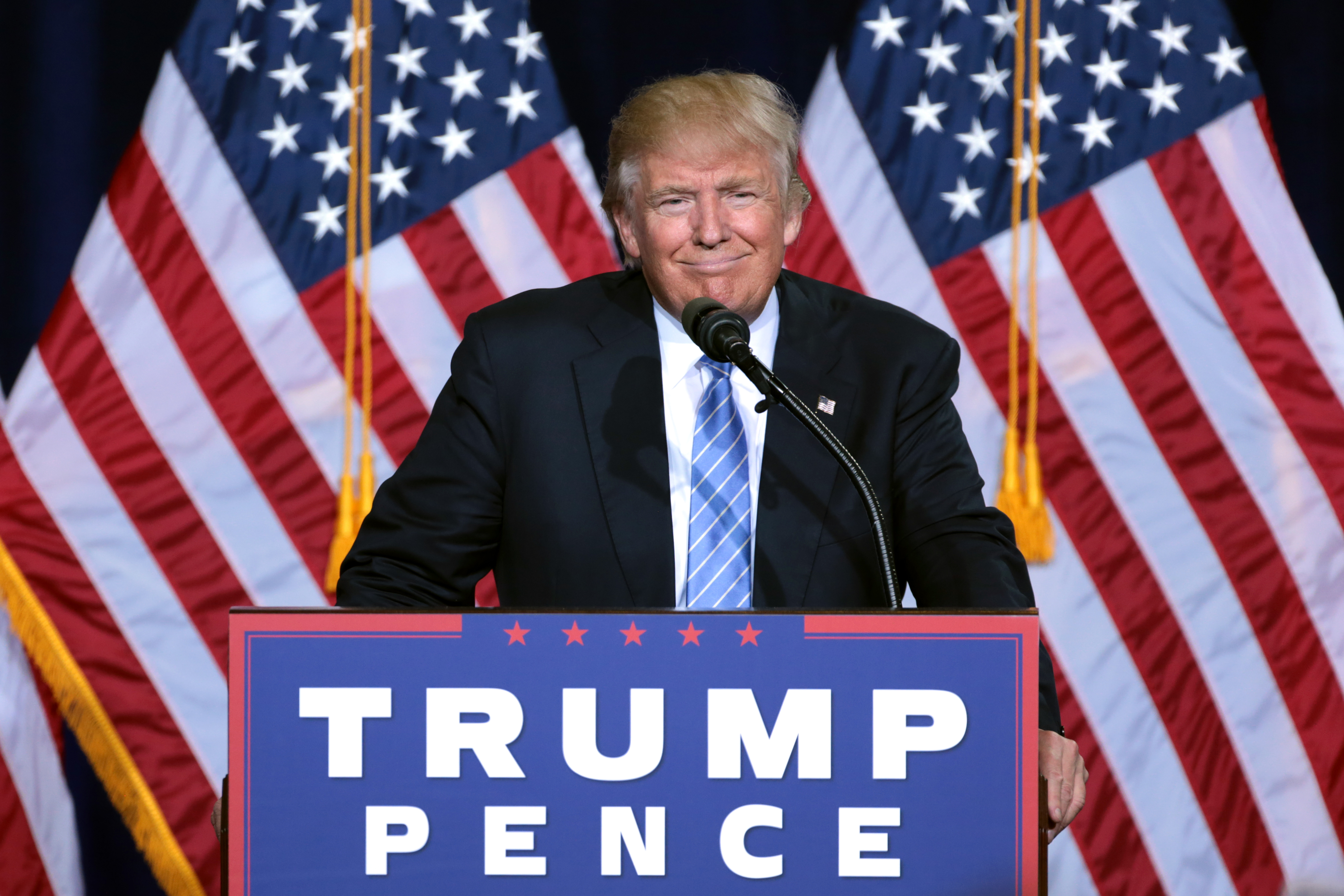 Donald Trump speaking at a campaign rally, flags in the background.