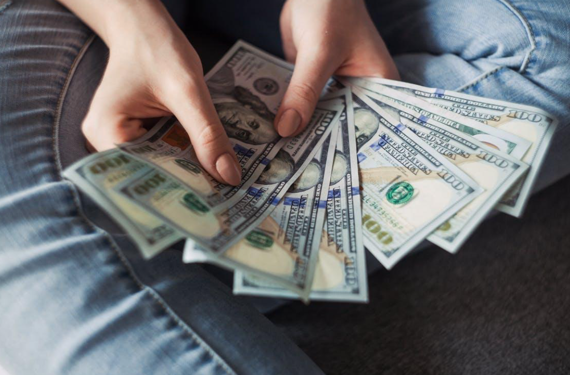 Person holding $100 bills; image by Alexander Mils, via Pexels.com.