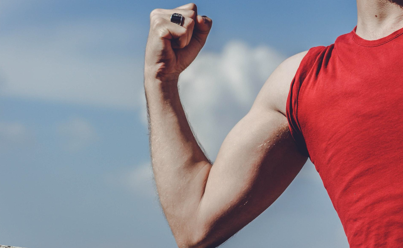 Man in red shirt raising his right arm; image by Samer Daboul, via Pexels.com.