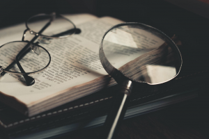 Gray magnifying glass and eyeglasses on top of open book; image by Wallace Chuck, via Pexels.com.
