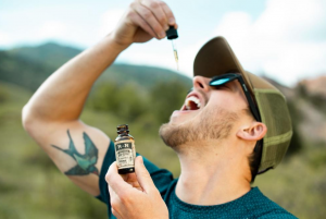 Colorado man taking hemp extract oil from a tincture outside; image by R+R Medicinals, via Unsplash.com.