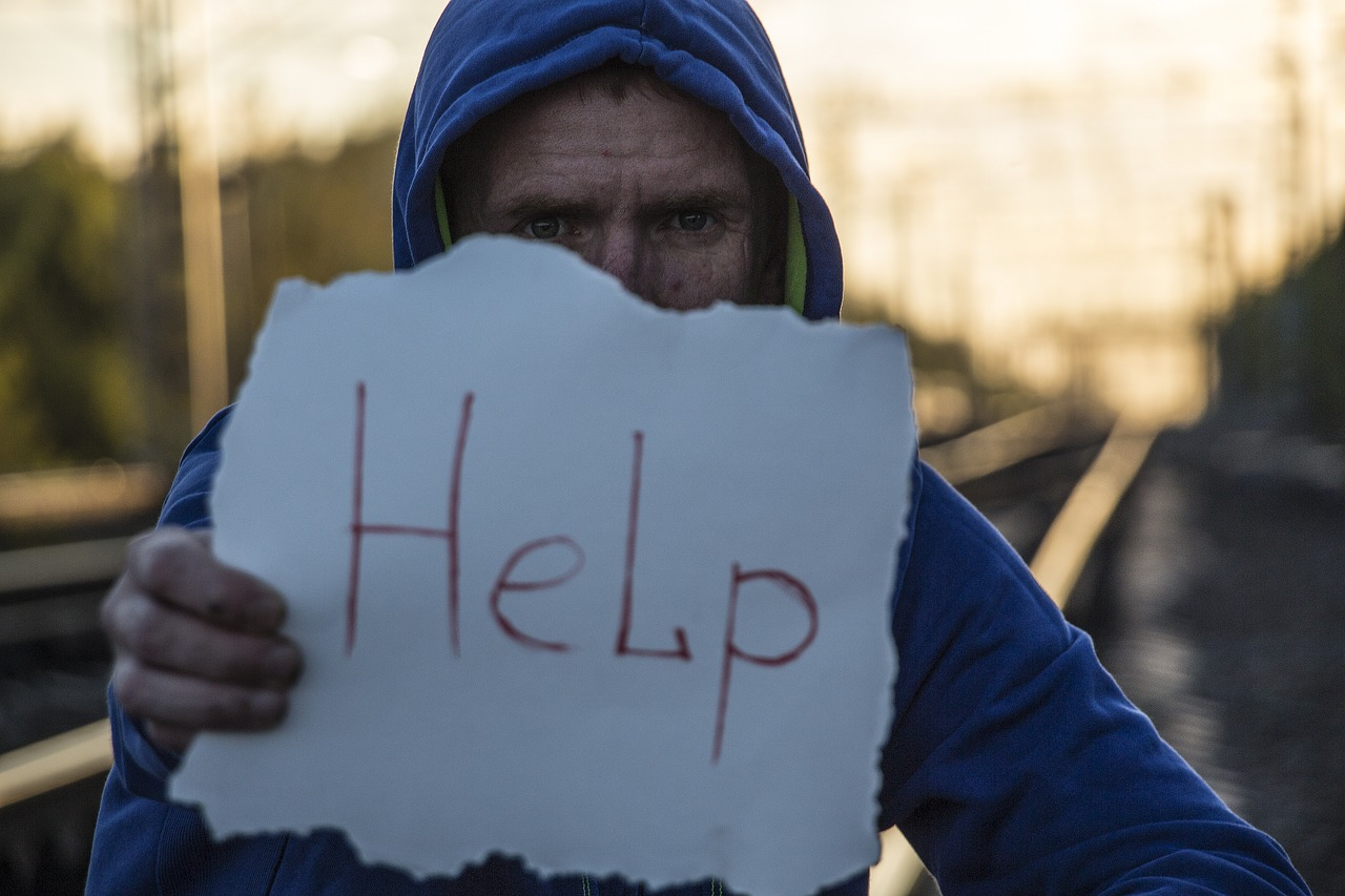Man holding a help sign