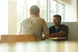Two men sitting in booth talking; image by LinkedIn Sales Navigator, via Unsplash.com.