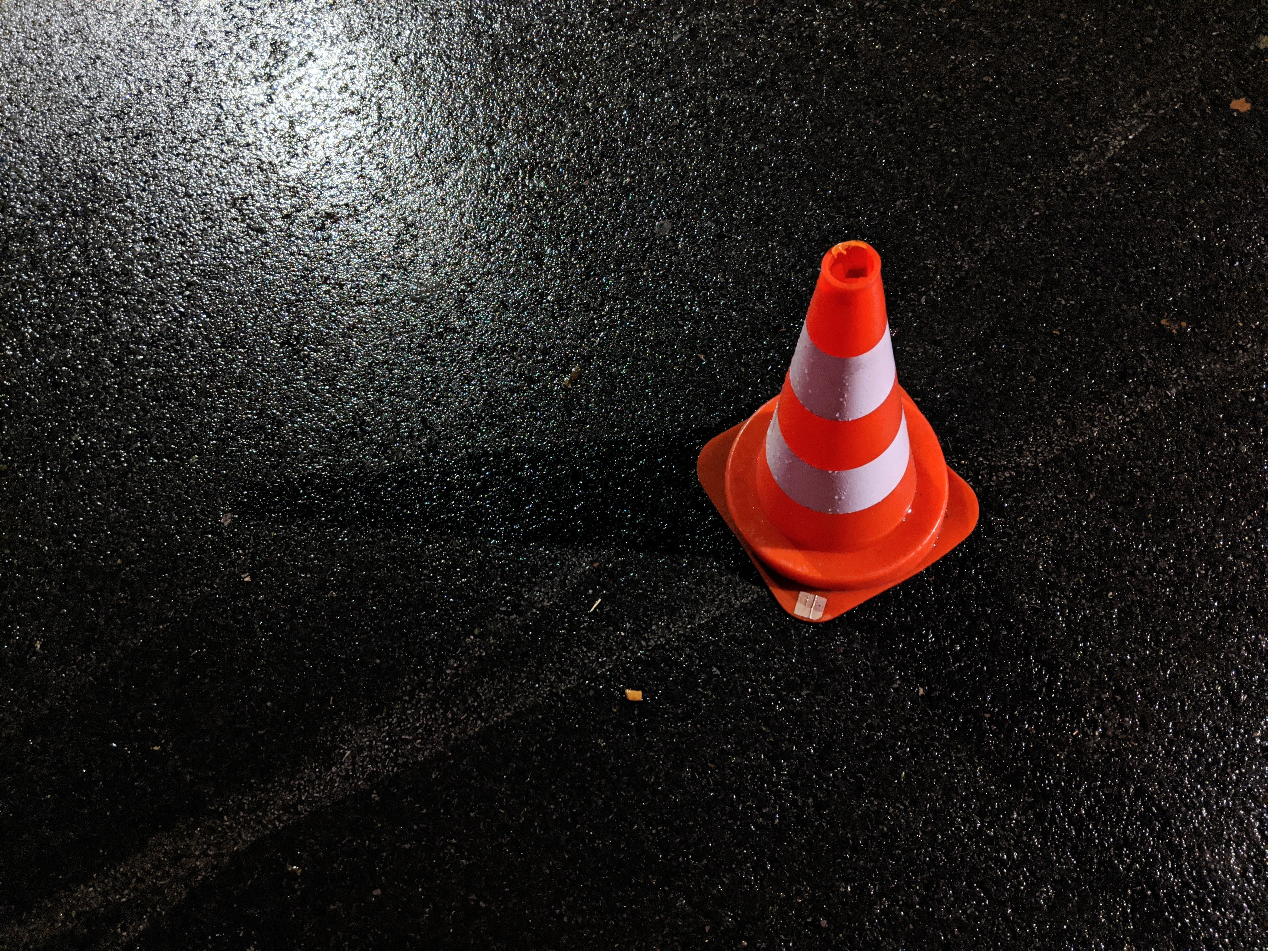 Traffic cone on dark, wet pavement; image by Lucian Alexe, via Unsplash.com.