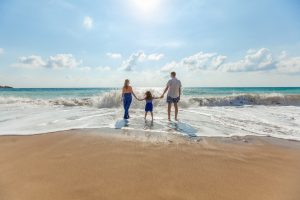 Family on the beach; image by Natalya Zaritskaya, via Unsplash.com.