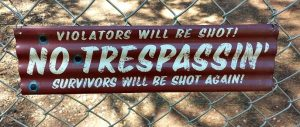 A No Trespassing sign which claims that violators will be shot, and survivors shot again.