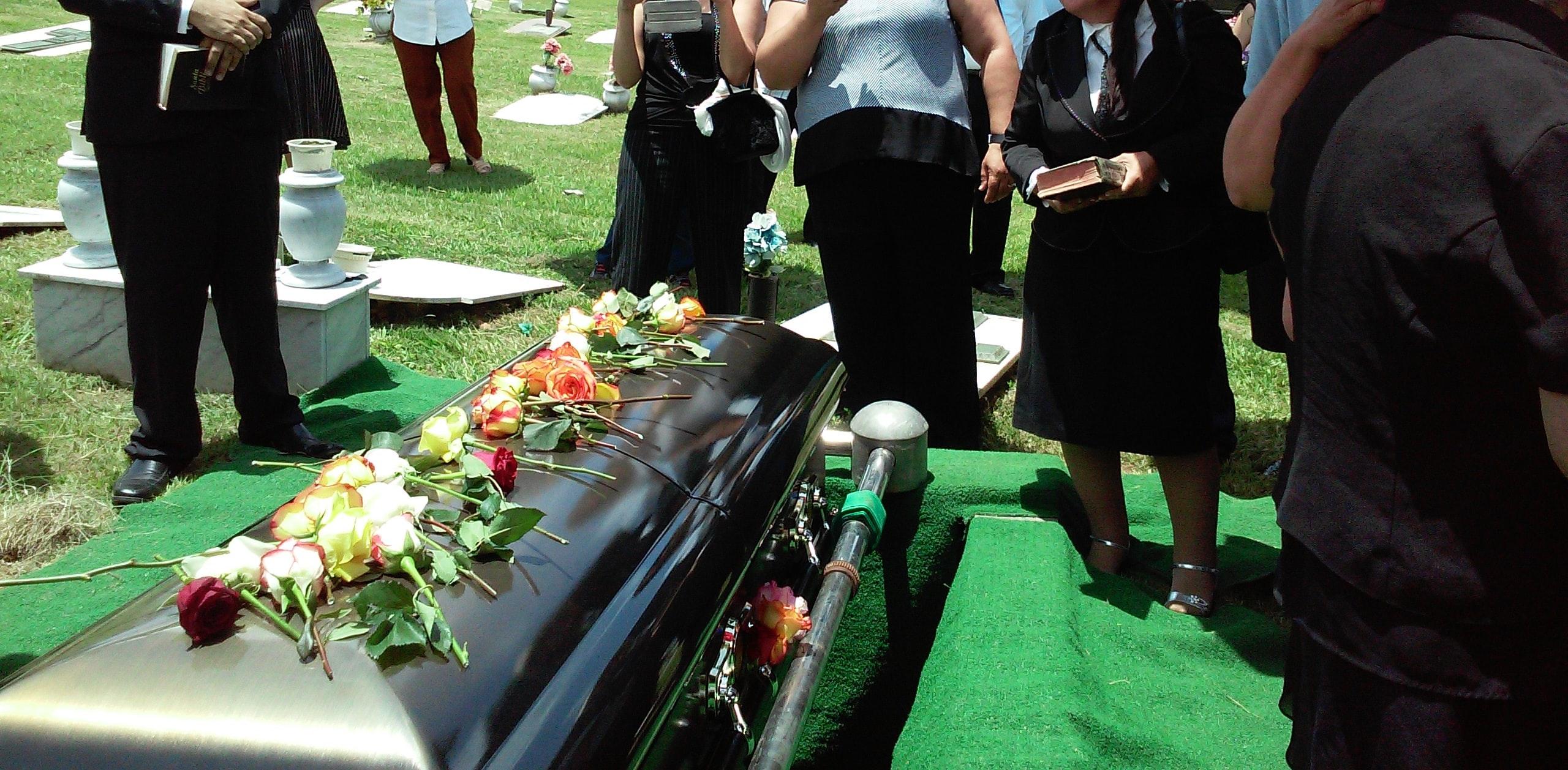 People gathered graveside for burial; image by Rhodi Lopez, via Unsplash.com.