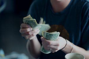 Woman counting dollar bills; image by Sharon McCutcheon, via Unsplash.com.