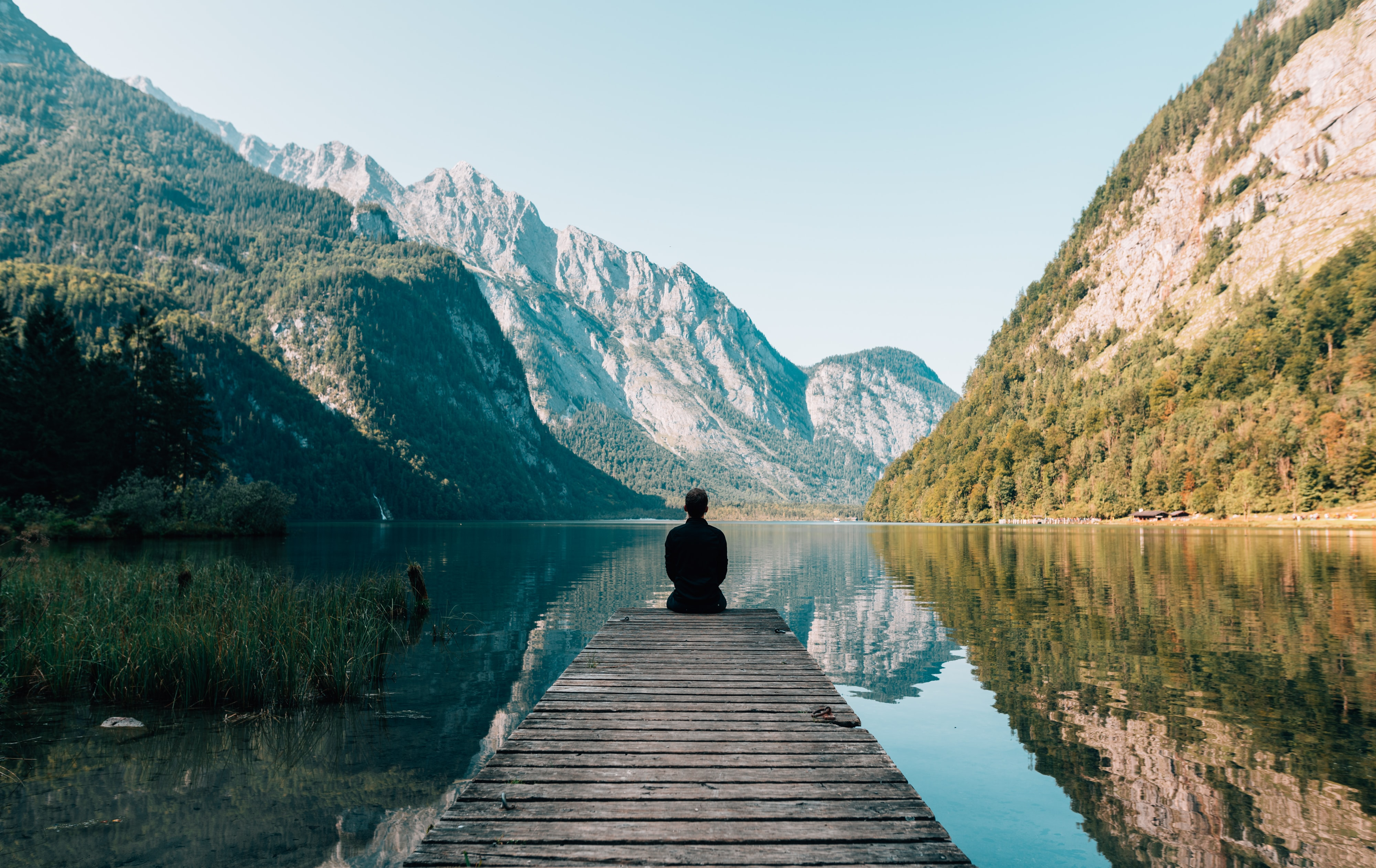 Man sitting on dock with his back to camera, watching still waters bordered by mountains; image by Simon Migaj, via Unsplash.com.