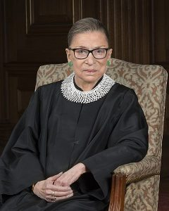 Ruth Bader Ginsburg, wearing her judicial robe and trademark collar, sitting in a chair.
