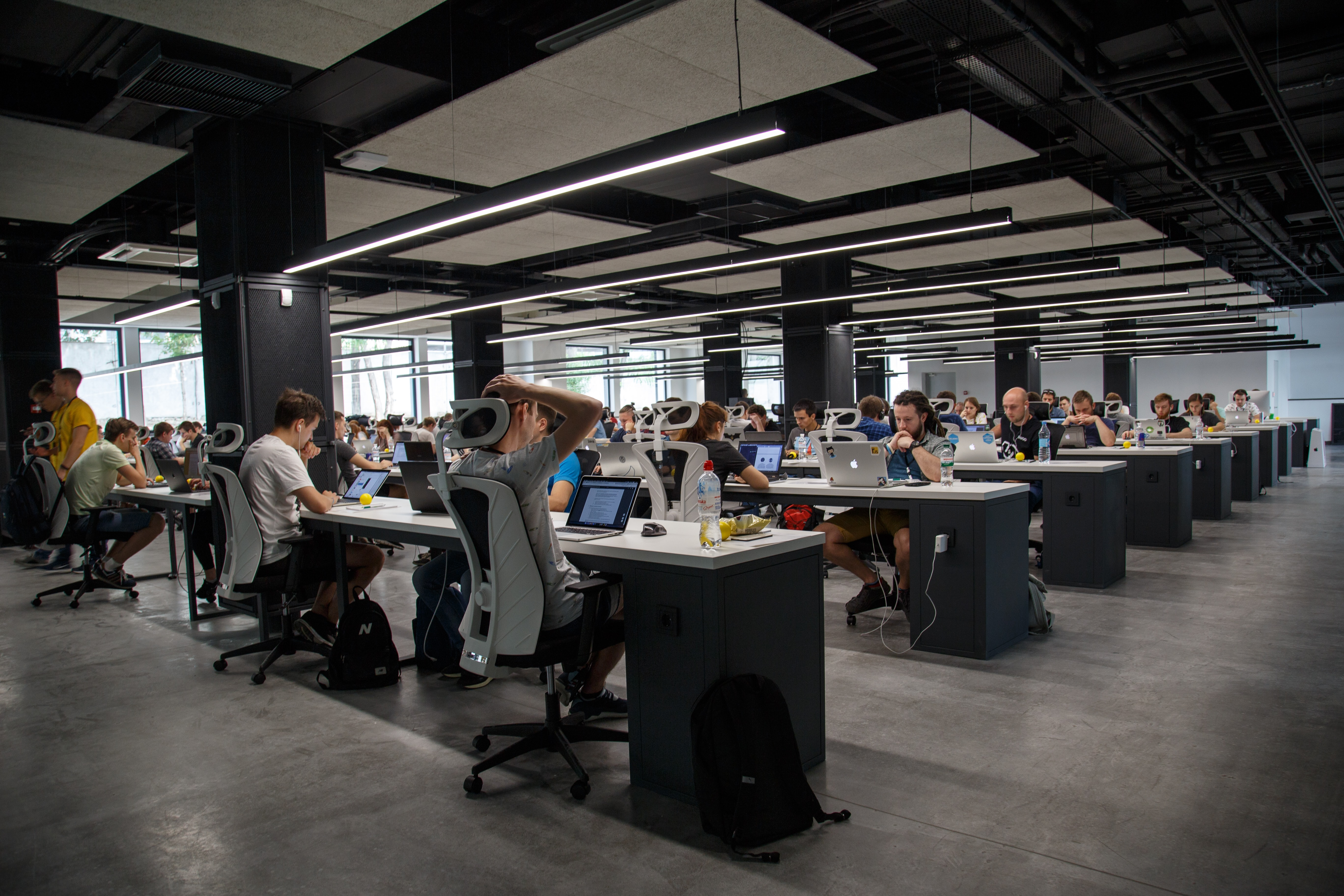 Open plan office space with rows of people working at long desks with no barriers.