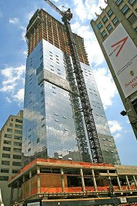 A glass-clad apartment high-rise during construction.