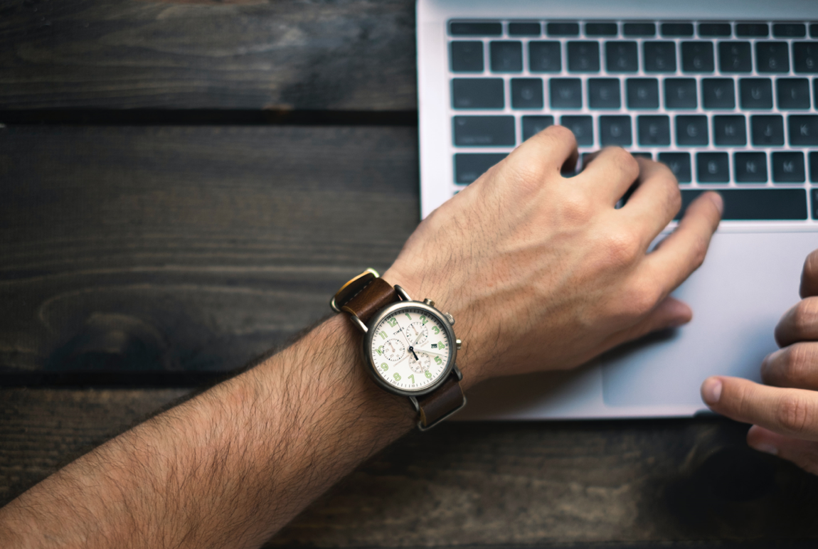 Man wearing a watch using a laptop; image by Brad Neathery, Via Unsplash.com.