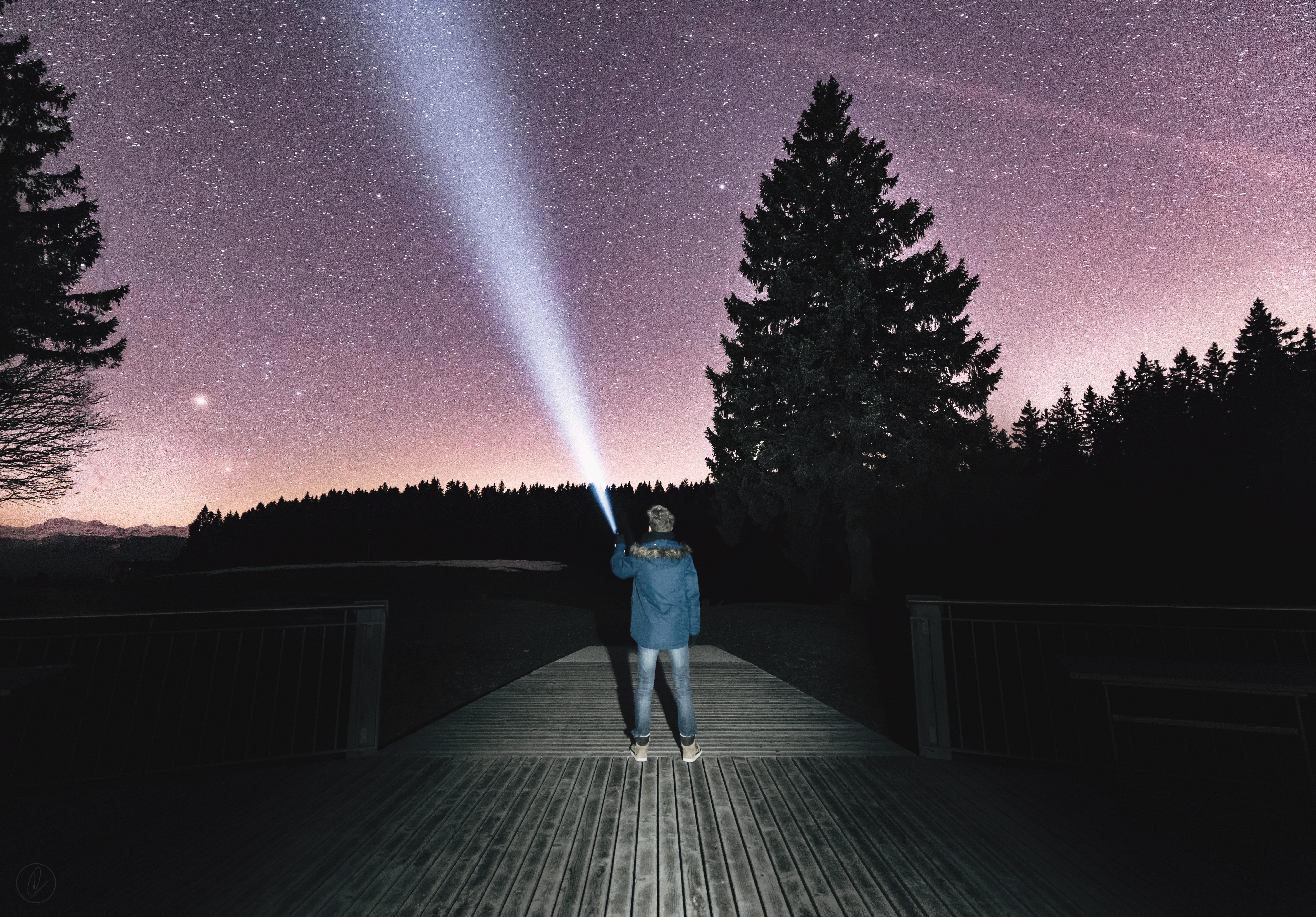 Man shining flashlight at star-filled night sky; image by Dino Reichmuth, via Unsplash.com.