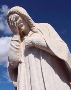A statue of Jesus, facepalming, in front of a deep blue sky.