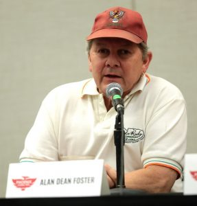 A man in a white polo shirt and faded red hat sits at a table at a convention.