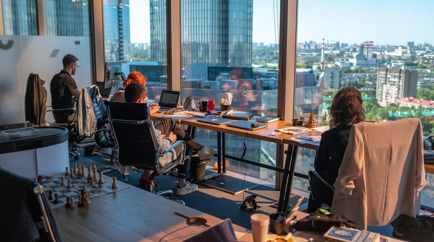 People sitting at workstations facing great view of city; image by Ant Rozetsky, via Unsplash.com.