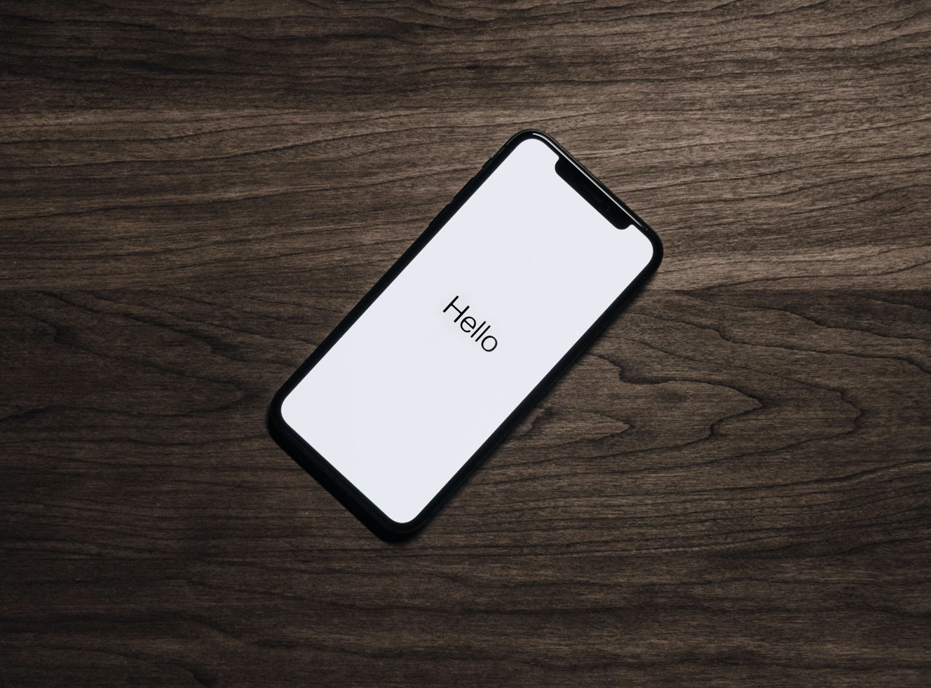 "Black smartphone with ""Hello"" on the screen, sitting on brown table; image by Tyler Lastovich, via Pexels.com."