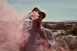 Man vaping outdoors, clouds of vapors; image by StockSnap, via Pixabay.com.