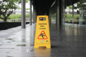 "Yellow ""Caution: Wet Floor"" sign on wet floor; image by T.H. Chia, via Unsplash.com."