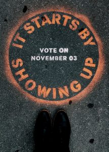 """Graffiti that reads, """"It Starts by Showing Up. Vote on November 3."""""""